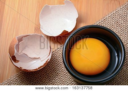 Fresh egg yolk in black bowl and on wooden table