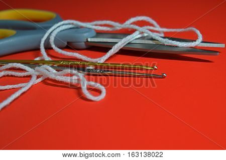 Crochet hooks yarn and scissors on a red background