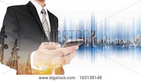 Businessman using smart phone, with double exposure telecommunication towers in sunrise and city, business network communication technology
