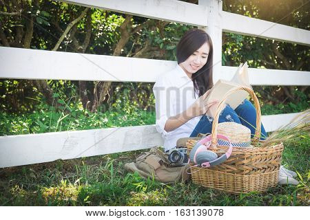 Pretty relaxed young asian woman reading a book at the lawn garen with sun shining vintage tone.