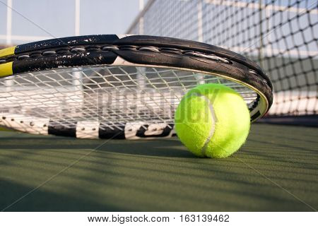 Tennis ball with a racket on hard court