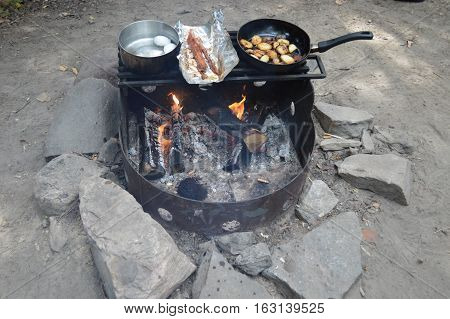 Campfire with hash browns, bacon and eggs cooking