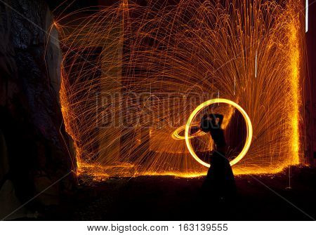 Showers of hot glowing sparks from spinning steel wool.
