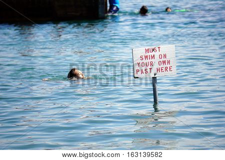 HARBOR SPRINGS, MICHIGAN / UNITED STATES - AUGUST 3, 2016: A sign indicates the limit beyond which swimmers must swim on their own at the Zorn Park Public Beach near downtown Harbor Springs.