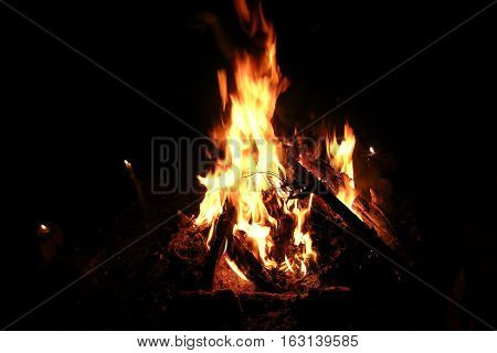 bonfire of logs and firewood at night and candles