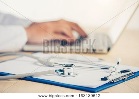 Medicine doctor's working table. Focus on stethoscope.