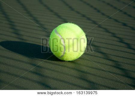 Tennis ball on hard court with sunlight