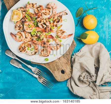 Seafood dinner. Grilled tiger prawns in white plate with lemon, leek and chili pepper on wooden serving board over bright blue background, top view. Slow food concept