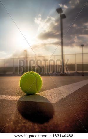 Tennis ball on hard court at sunset