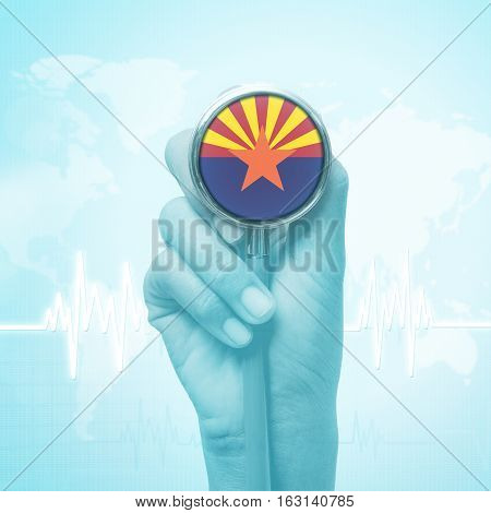 hand holding stethoscope with Arizona flag .