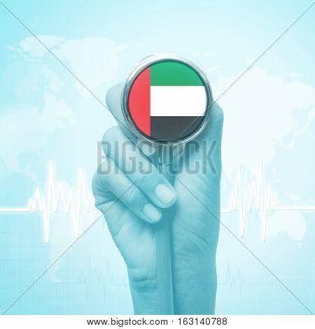 hand holding stethoscope with United Arab Emirates flag.
