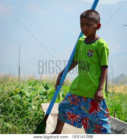Burmese Boy Rowing Wooden Boat
