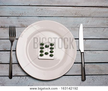 Diet or medicine abuse concept - green pills in plate with knife and fork on wooden grunge table.