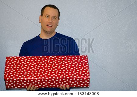Tired of gift giving? Man holding large gift.