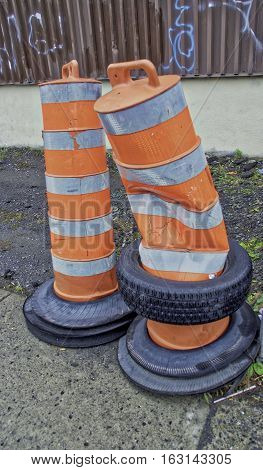 2 Orange construction cylinders and one is poked and have black tire