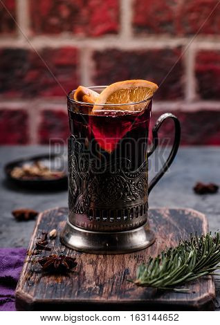 Mulled wine with orange and spices in vintage glass cup holder on wooden board. Concrete background. Hot drink.
