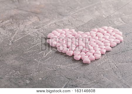Heart shaped candies in shape of heart on gray background. valentine's day background