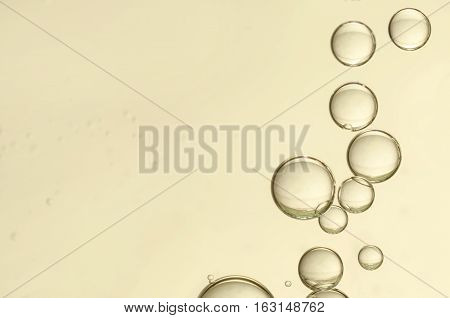 Golden fizz bubbles flows over a light background