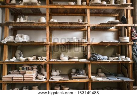 Wooden racks in a pottery workshop in which there are pottery many different pottery standing on the shelves in a potery workshop. Low light