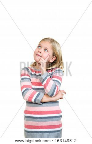 Little daydreamer. Cheerful little girl holding finger on chin and looking away while standing isolated on white