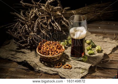 Glass of beer with wheat and hops, basket of pretzels on linen cloth on wooden table