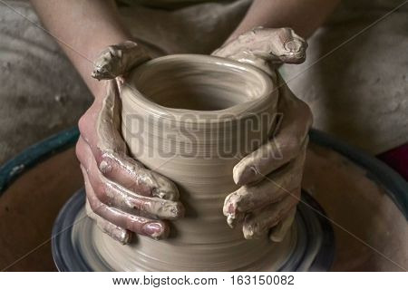 Creating a jar or vase of white clay close-up. Master crock. Man hands making clay jug macro. The sculptor in the workshop makes a jug out of earthenware closeup. Twisted potter's wheel. poster