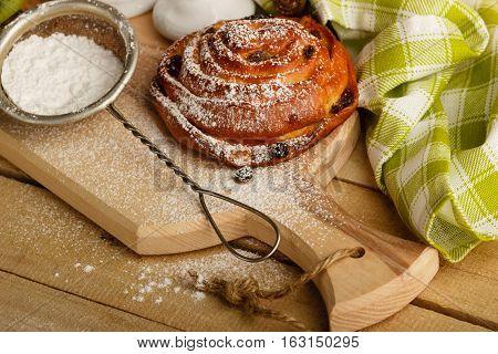 Bun With Raisins And Sugar Powder In The Strainer