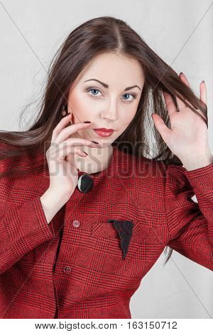 Portrait of beautiful young woman in red jacket hand adjusts his hair