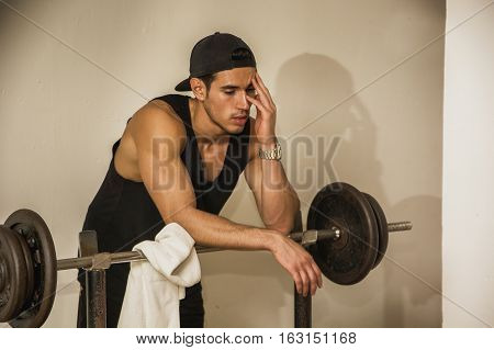Handsome young athletic man resting on barbell rack after workout in gym