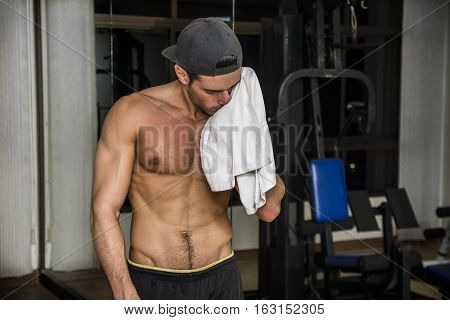 Muscular young man drying sweat from his face with a towel after workout in a gym