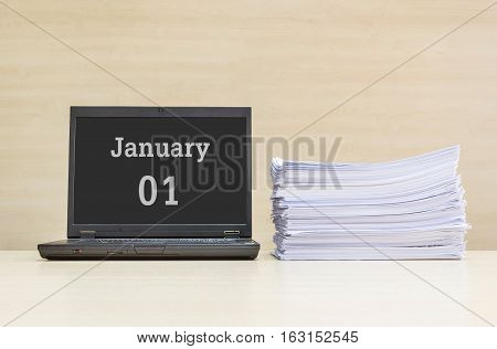Closeup computer laptop with january 1 word on the center of screen in calendar concept and pile of work paper on wood desk and wood wall in work room textured background with copy space