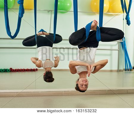Young woman doing aerial yoga exercise or yoga indoor. Fitness, stretch, balance, exercise and healthy lifestyle people. Woman using hammock.