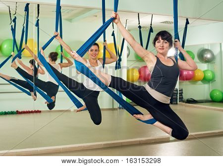 Young women doing aerial yoga exercise or yoga indoor. Fitness, stretch, balance, exercise and healthy lifestyle people. Women using hammock.