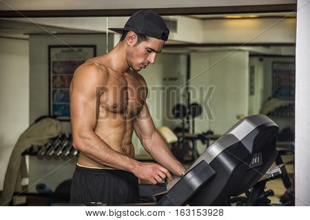 Shirtless muscular attractive young man running on treadmill, in a gym