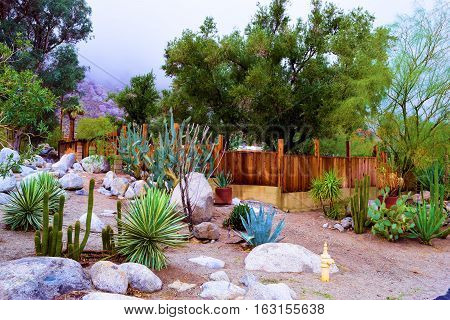 Residential home including a wooden rustic fence with a rock and cactus garden taken in the desert