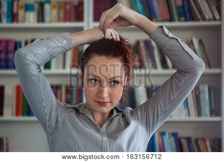 Redhead Girl Making Her Hair In The Library