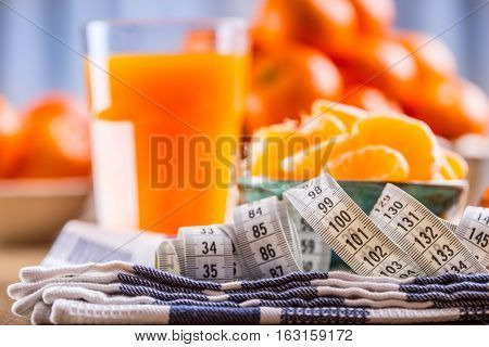 Fresh tropical fruit and measure tape. Tangerines peeled tangerine and tangerine slices on a blue cloth. Mandarine juice.