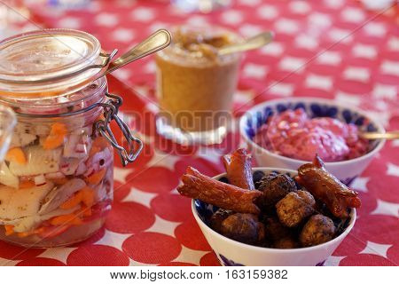 Home made pickled herring onion and carrot in a glass jar meatballs sausage beetroot salad and mustard on the Christmas table with a red cloth