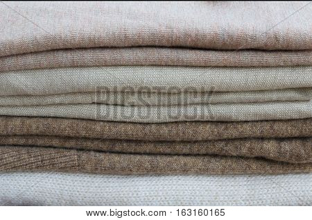 Close up of sweaters and cardigans. Stack of knitted clothes in beige tones for texture or background.