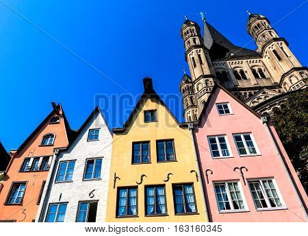A row of colorful houses on the banks of the Rhine in front of the St. Martin Church in Cologne, Rhineland, Germany