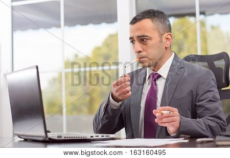 Portrait Of Ambitious Young Businessman Who Is Smoking After Failure