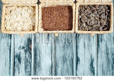Sunflower linseed and pumpkin seeds in bamboo baskets on a wooden board.