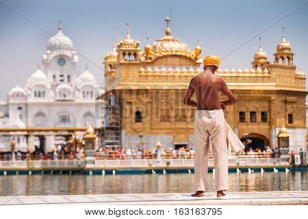 Sikh pilgrim prepearing to immerse in holy tank near Golden Temple (Sri Harmandir Sahib), Amritsar