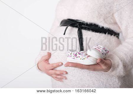 Photo Of Pregnant Woman Holding Baby Shoes