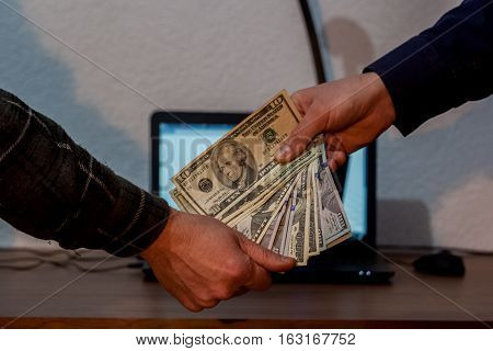 Two Guys Or Businessmen Giving Dollars To Each Other. Laptop In The Background
