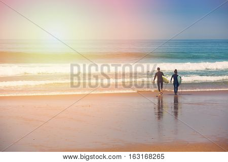 young surfer couple going into the ocean at sunrise. Portugal Algarve