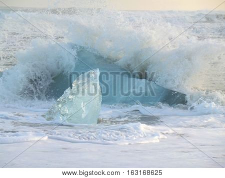 Powerful wave clashing a huge iceberg on the beach of South Iceland