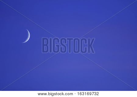 Rising crescent moon in blueish evening sky.