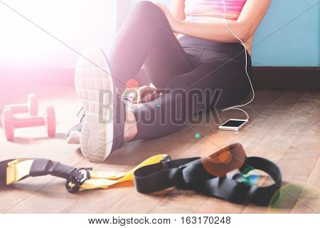 Female fitness resting and relaxing after workout. Woman sitting down on wood floor. Sport Fitness Healthy lifestyle concept