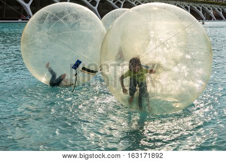 Valencia Spain - May 18 2014: Children have fun inside plastic balloons on the water. The Magic of Childhood.
